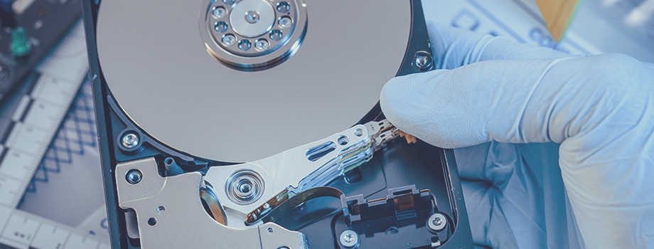 Blue gloved hands handle a hard drive with exposed internals.