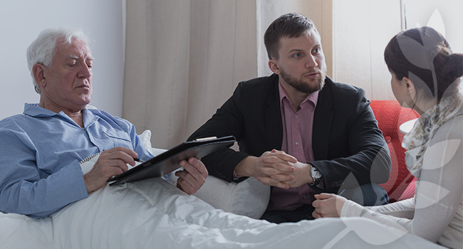 Social worker speaking with cancer patient and family member next to hospital bed.