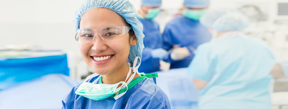 Smiling female nurse faces camera in operating room as surgeons and assistants work on patient in the background.